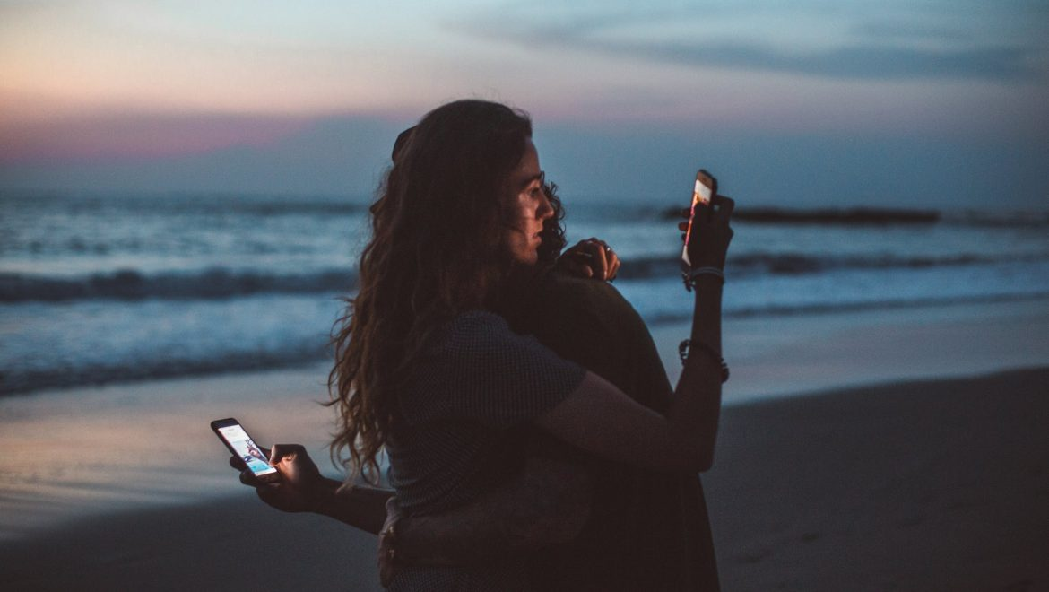 couple-hugging-on-phones-smartphone-addiction-signs-symptoms-tips-expat-nest